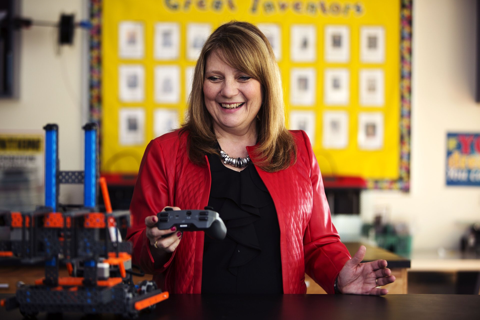 Debbie Huffine, ACE doctoral student, demonstrates with a robot built by the students in her class.
