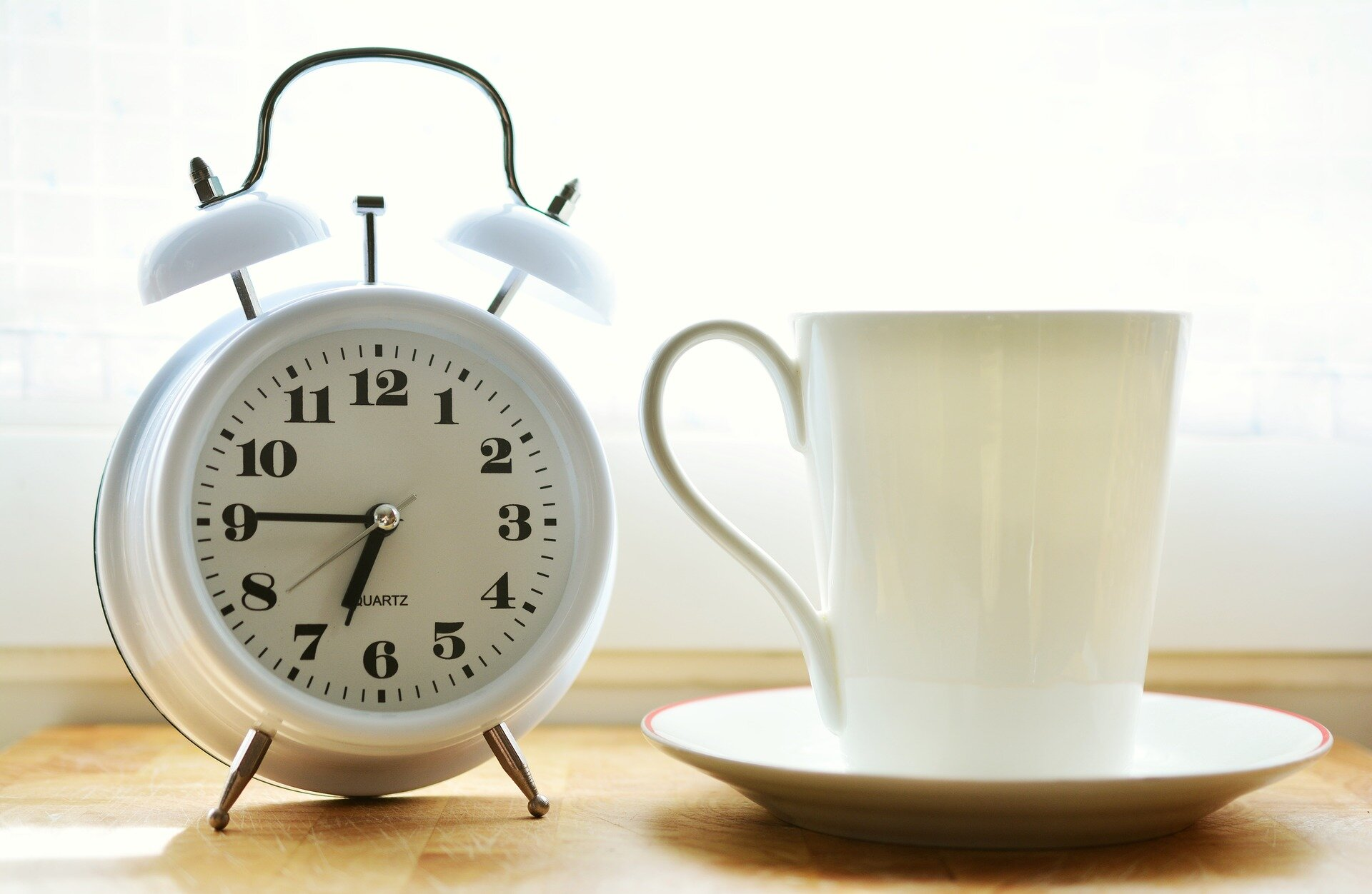 Alarm clock next to cup of coffee
