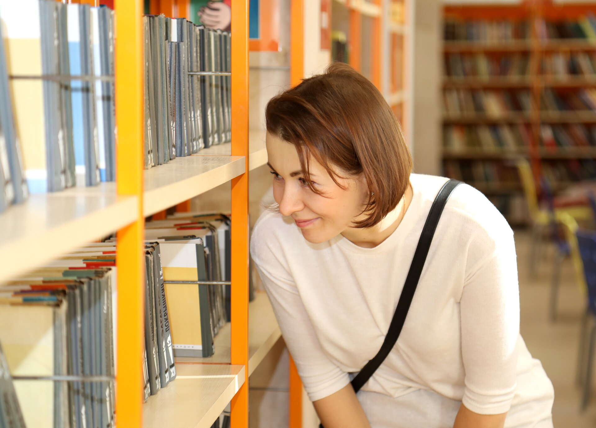 Woman browsing rows of bookcases