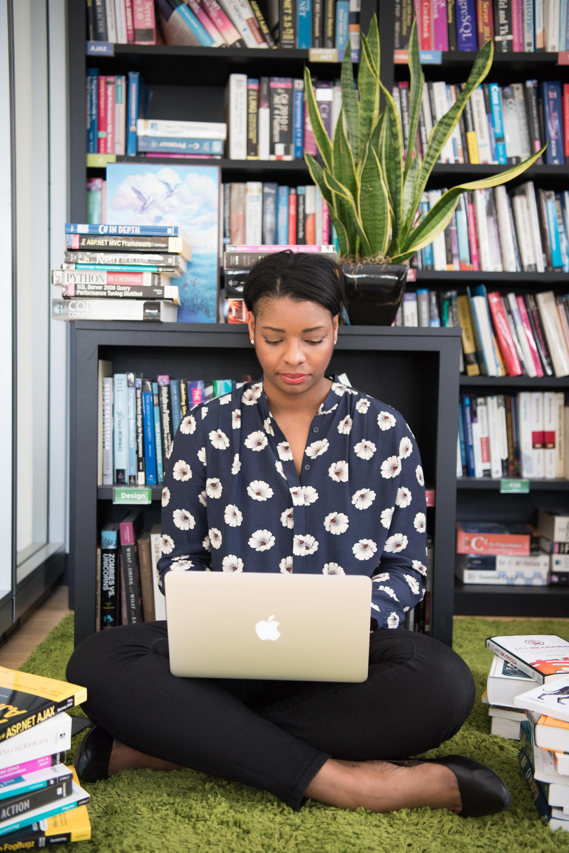 Woman on Mac in front of bookcase