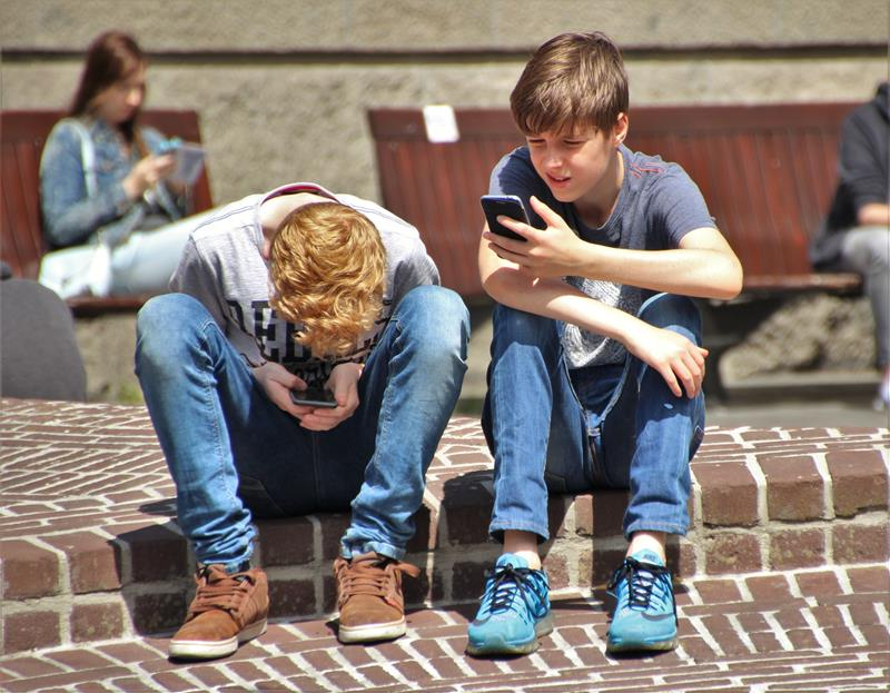 Boys on cellphones at the playground